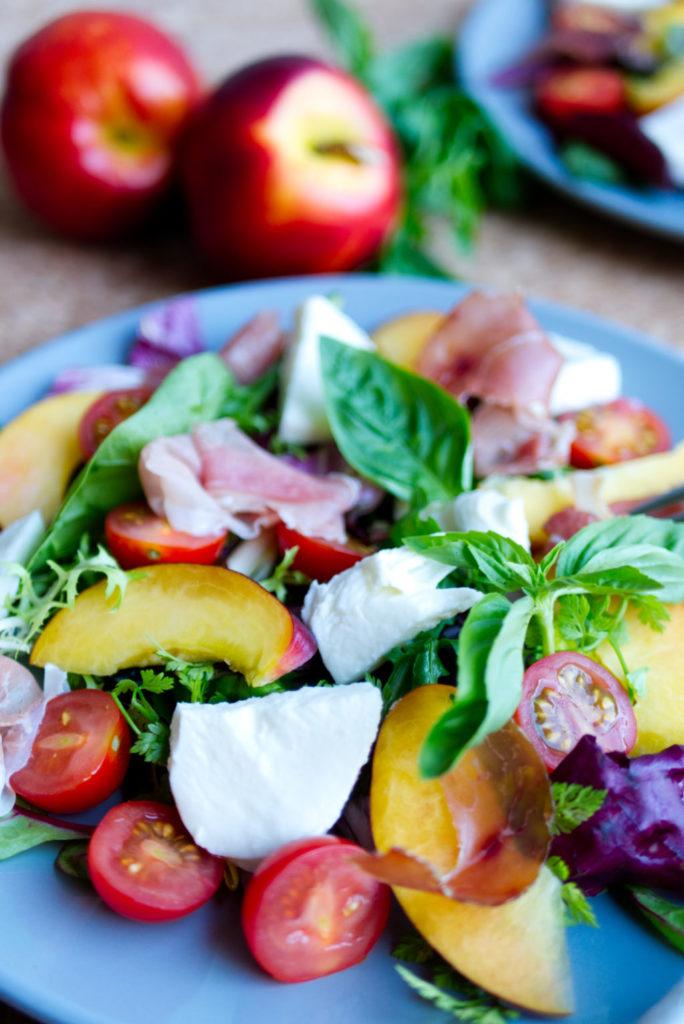 Dieser herrlich-sommerliche Nektarinen-Salat mit Mozzarella, Kirschtomaten, Basilikum, Pflücksalat und westfälischem Knochenschinken bringt den Sommer auf den Teller. Abgerundet wird der Salat mit einem schnellen Dressing aus Olivenöl und Crema Balsamico. Ein Rezept, das einfach glücklich macht! Panama Quadrat – der Foodblog aus Münster
