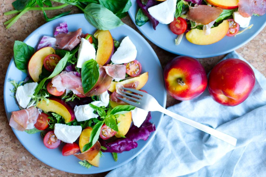 Der sommerliche Salat mit frischen Nektarinen, Mozzarella, Kirschtomaten, Pflücksalat, Basilikum und westfälischem Knochenschinken auf einem Teller angerichtet und von oben fotografiert. Panama Quadrat – der Foodblog aus Münster