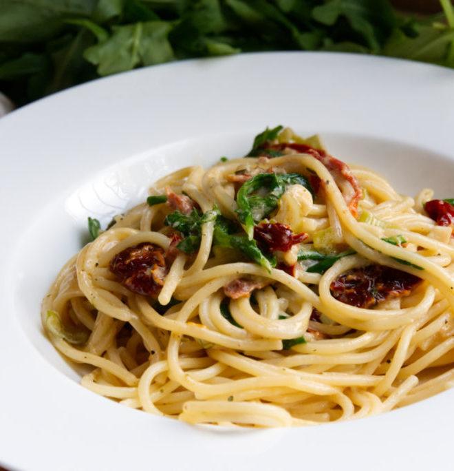 Spaghetti mit getrockneten Tomaten und Rucola in einem tiefen Teller serviert. | Lieblingsrezept | Panama Quadrat