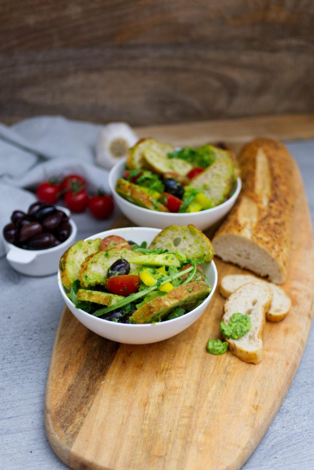 Mediterraner Brotsalat mit Pesto, Kalamataoliven, Ciabatta, kleinen Tomaten, Rucola und Basilikum. Angerichtet in kleinen Schüsseln. | Das Rezept | Panama Quadrat – der Foodblog aus Münster