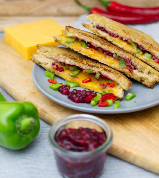 Grilled Cheese Sandwich: Angerichtet auf einem Teller, davor eine grüne Spitzpaprika und ein Glas mit Preiselbeeren. | Panama Quadrat